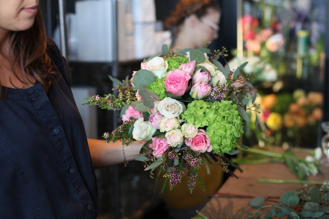 Florist Showing Off Floral Arrangement With Pink And White Roses And Green Hydrangeas